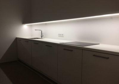 Einbauküche mit Kochfeld, Kühlschrank und verdeckt liegenden Schubkästen.