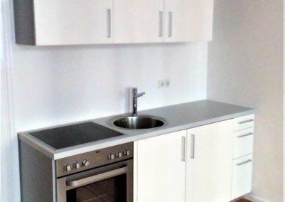 Kleine, kompakte Einbauküche mit Einbauherd, Kochfeld und Spüle.